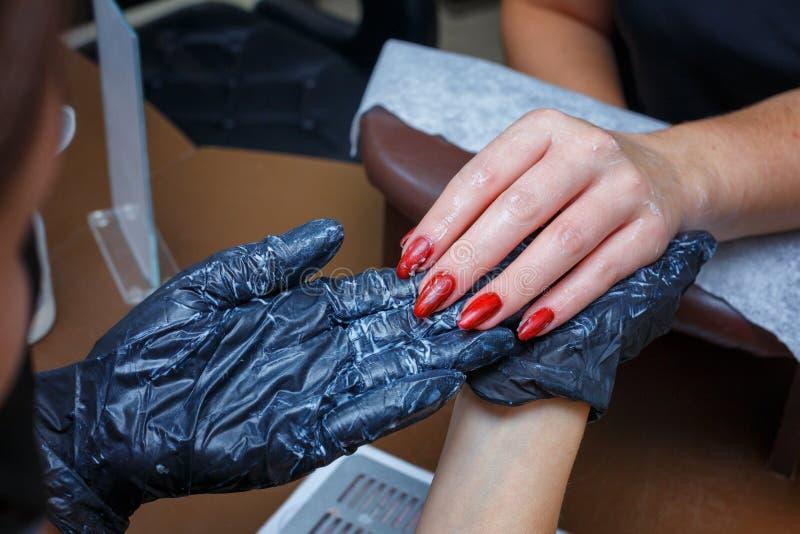 手关心沙龙修指甲,大师润湿客户奶油的手 图库摄影