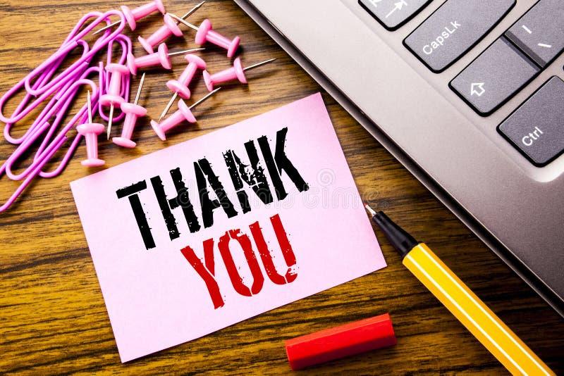 手写的文本陈列感谢您 在木backgrou的桃红色稠粘的便条纸写的谢意感谢的企业概念 免版税库存照片