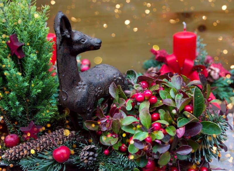 手制作了美好的从新绿色冷杉分支霍莉莓果槲寄生驯鹿蜡烛的圣诞节植物的花卉构成 图库摄影