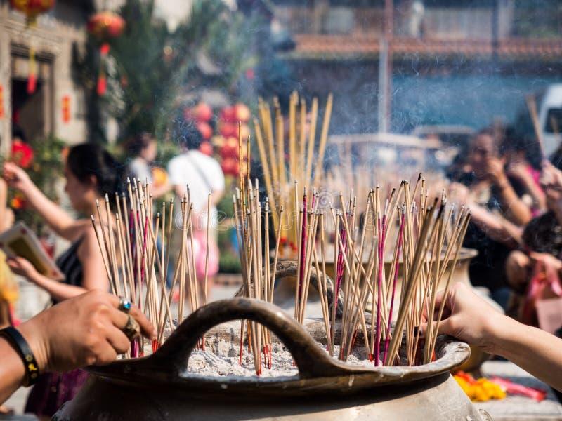 手刺中在香罐燃烧的香火棍子,并且烟曾经致以对菩萨的尊敬 免版税库存照片