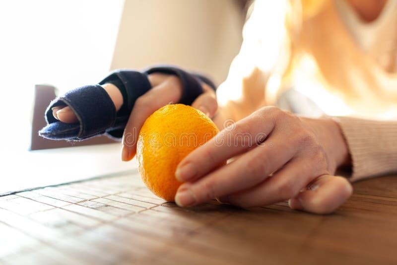 手剥与医疗手吊索的一个桔子 免版税库存图片