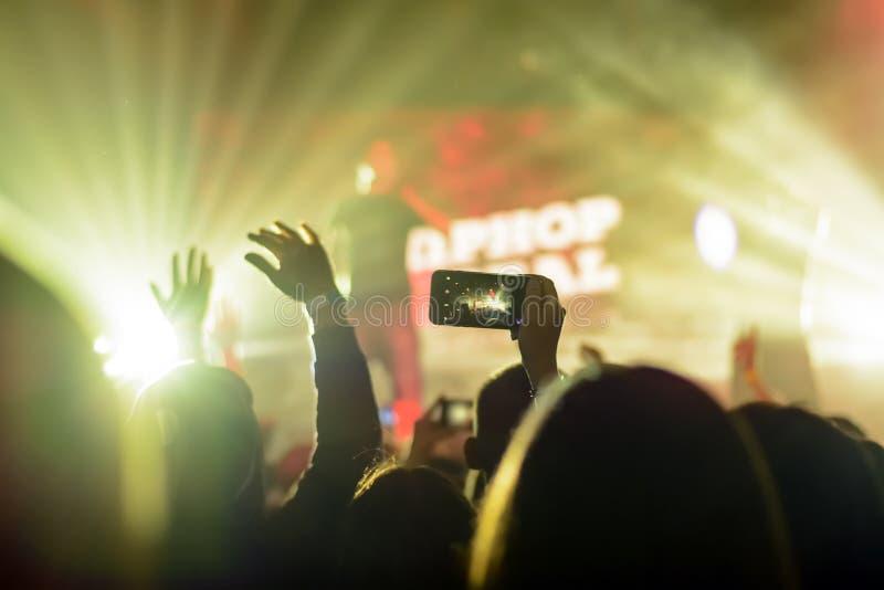手剪影有一个智能手机的在音乐会 库存照片