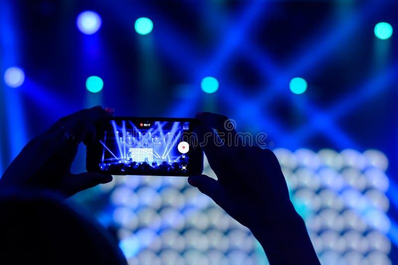 手剪影有一个智能手机的在音乐会 免版税图库摄影