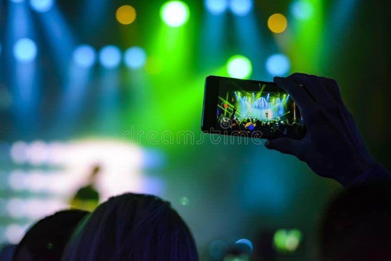 手剪影有一个智能手机的在音乐会 库存图片