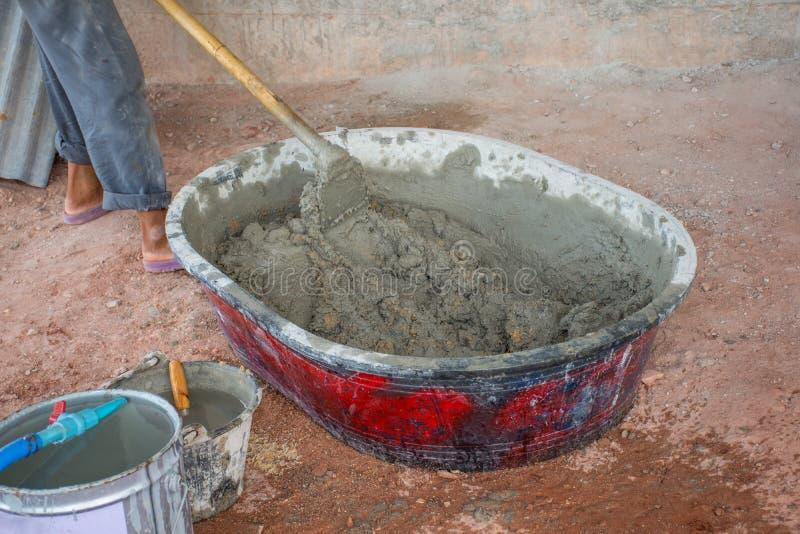 手动地混合在搅拌器盘子的建筑工人混凝土 免版税库存图片