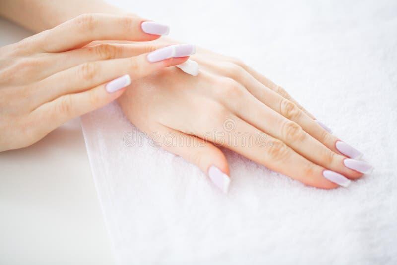 手和钉子关心 有完善的修指甲的美好的妇女` s手适用于奶油皮肤手 秀丽天温泉修指甲 免版税库存照片