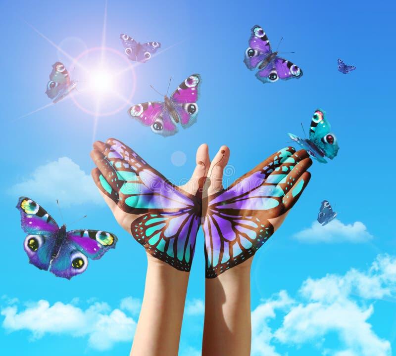 手和蝴蝶递绘画,纹身花刺,在蓝天。 免版税库存照片