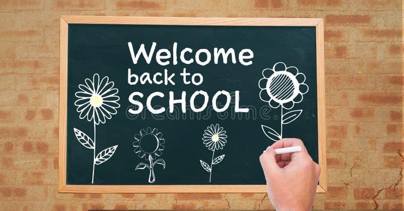 手回到学校课文和花的图画欢迎在黑板 免版税库存图片
