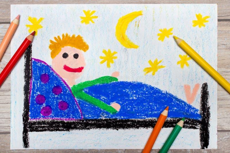 手图画和蜡笔:在床上的微笑的小男孩 免版税库存图片