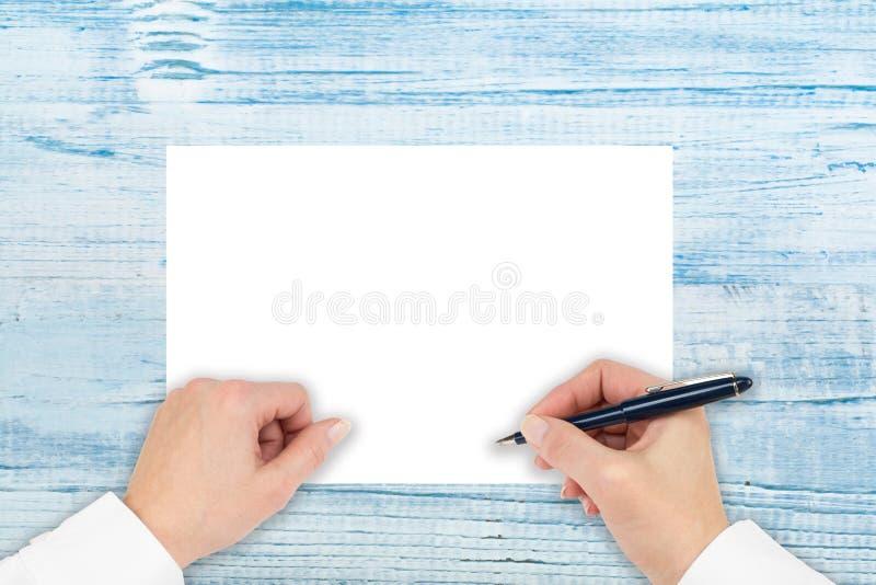 手在一张木桌上的一张纸书写 做笔记,做计划,写,凹道 r 库存照片