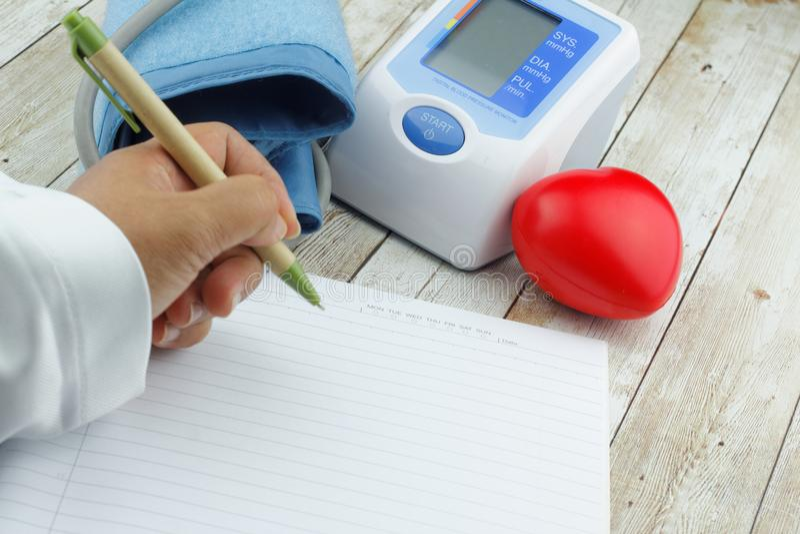 手在与血压显示器米和心脏形状标志的空白的空的纸书写在木桌上 库存照片