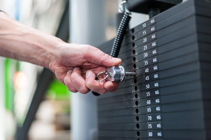 手在健身俱乐部的调整重量 免版税库存图片