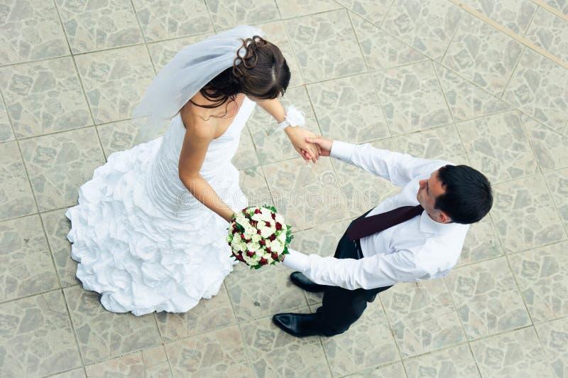 手在手上。爱恋的新娘和新郎顶视图  库存图片