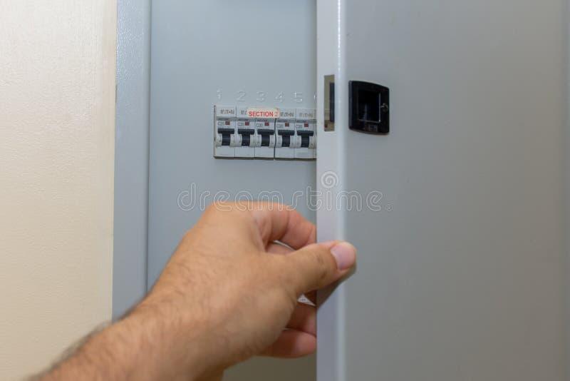 手在看电子破碎机的住宅房子里打开保险丝箱子固定力量损失  库存图片