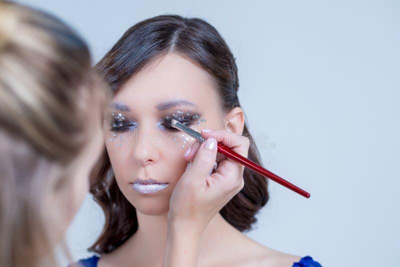 手在眼睛投入阴影颜色一美丽的少女 应用明亮的颜色眼影膏的化妆师 创造性的艺术 库存图片