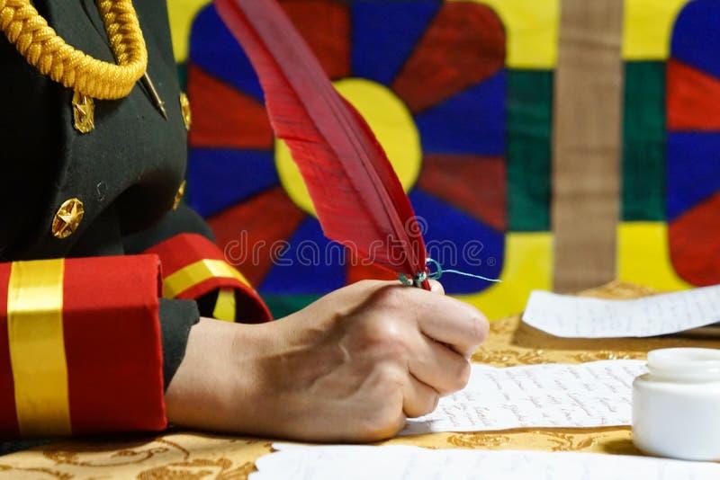 手在羊皮纸写红色翎毛钢笔 免版税库存图片