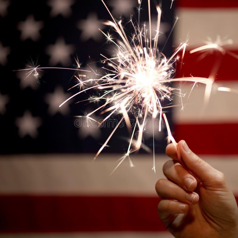 手在美国国旗前面的藏品闪烁发光物第4的7月庆祝 库存图片