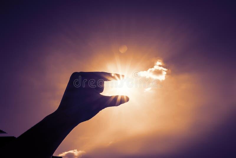 手在蓝天和云彩,葡萄酒fil的采摘太阳剪影  免版税图库摄影