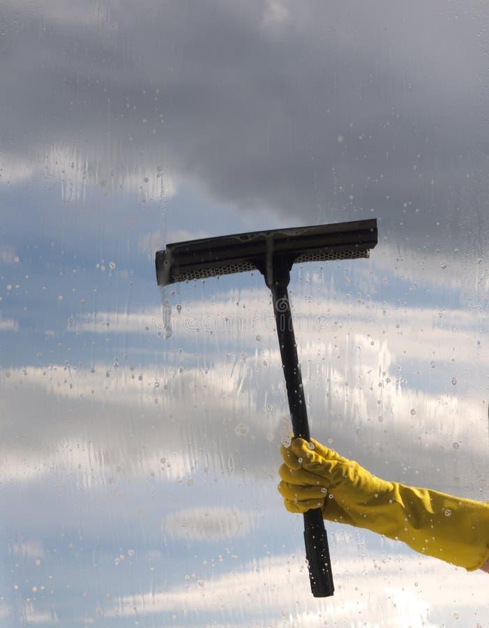 手在防护手套在多云天空背景的清洁窗口里  库存照片