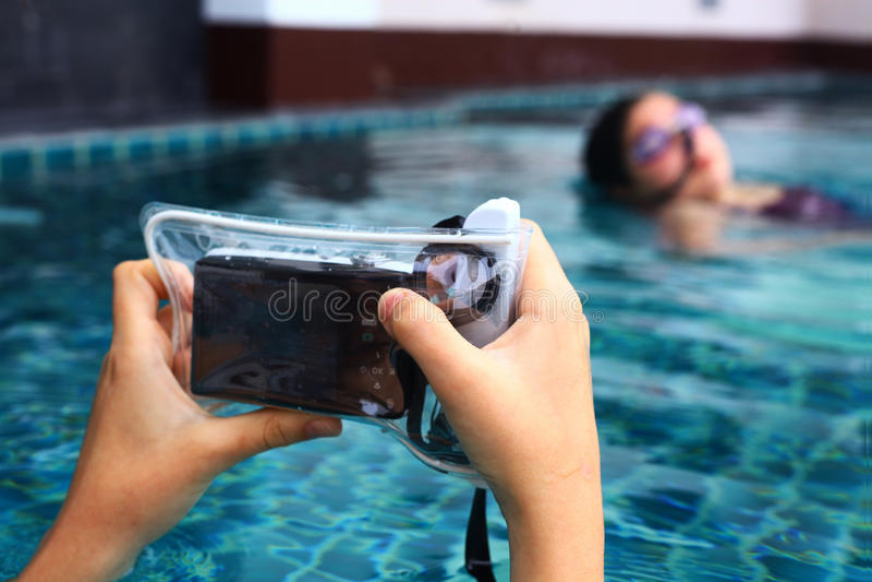 手在防水沙发套覆盖物的举行照相机 图库摄影