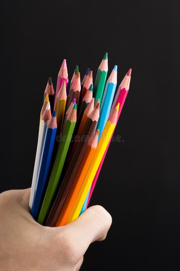 手在黑背景特写镜头的捆绑铅笔 免版税图库摄影