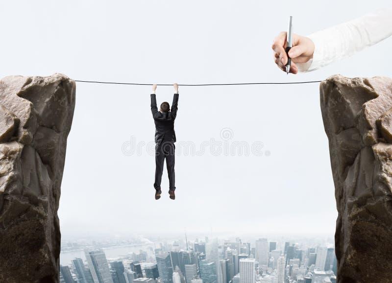 手垂悬由绳索的图画商人 库存图片