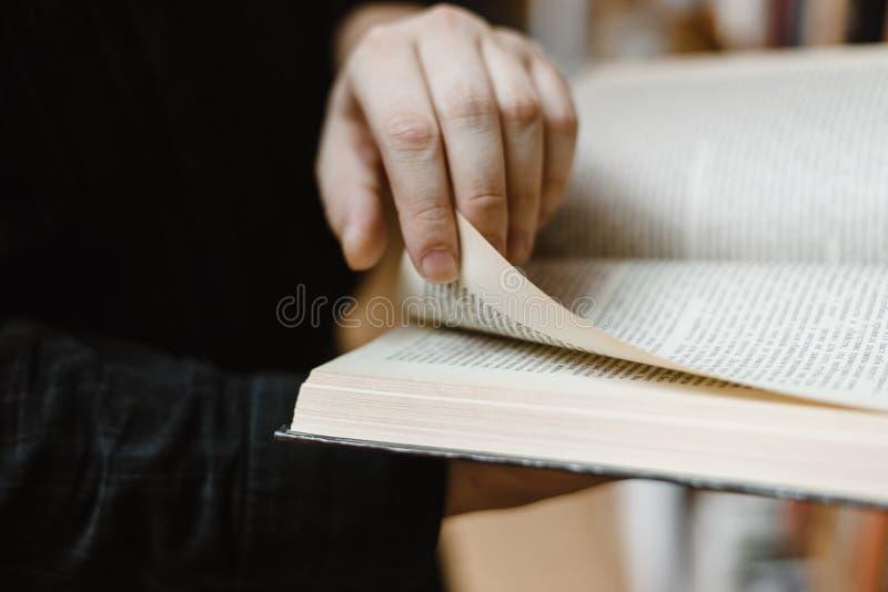 手大书在这本书的将转动页对下个章节 免版税库存照片