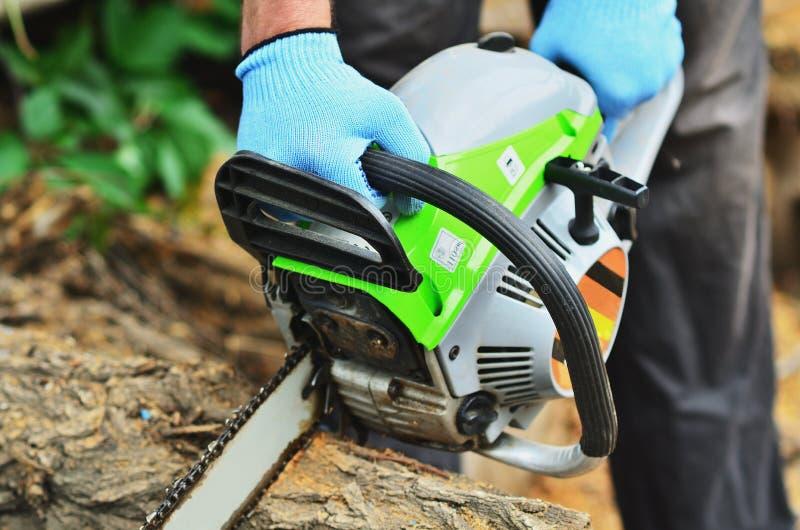 手套的一个人锯与锯的一本日志 免版税图库摄影