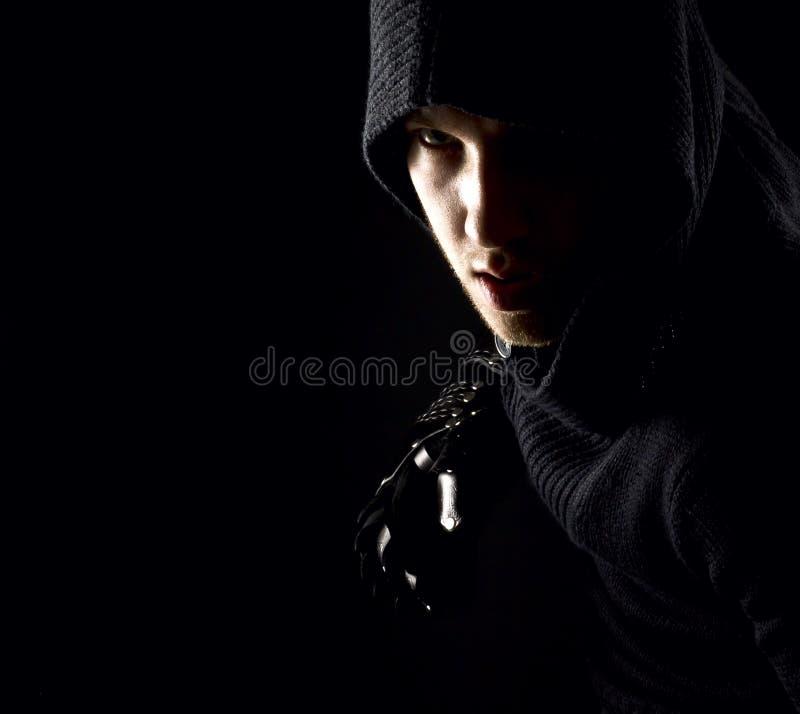 手套的情感,年轻和可爱的刺客在黑背景 库存图片