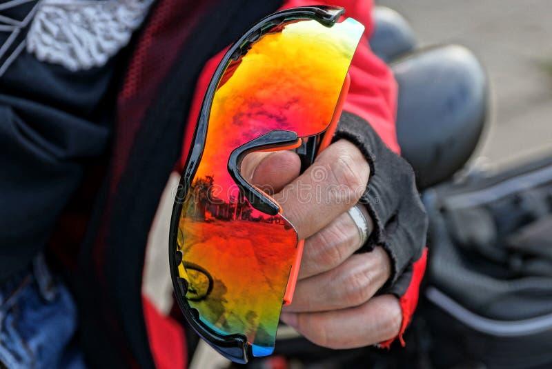手套的手拿着色的体育玻璃 皇族释放例证