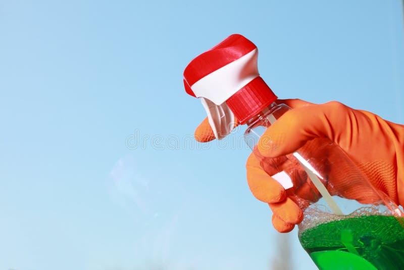 手套的手清洁窗口旧布和浪花 免版税图库摄影