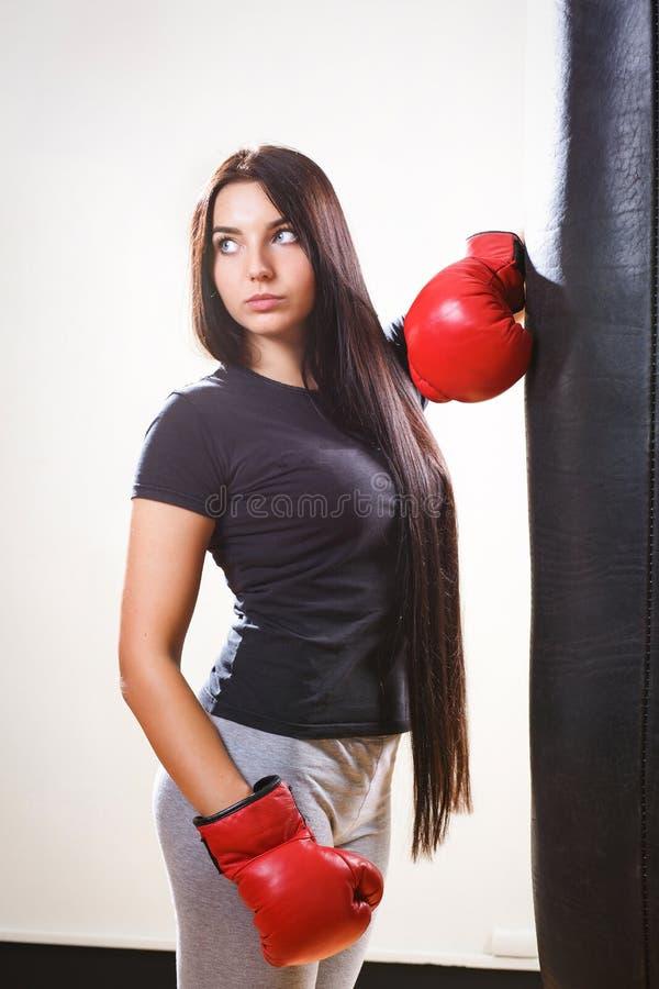 手套的深色的拳击击中梨的女孩和身体 图库摄影