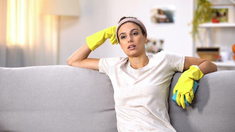 手套的被用尽的妇女坐沙发,疲乏的主妇的清洗的服务 免版税库存照片