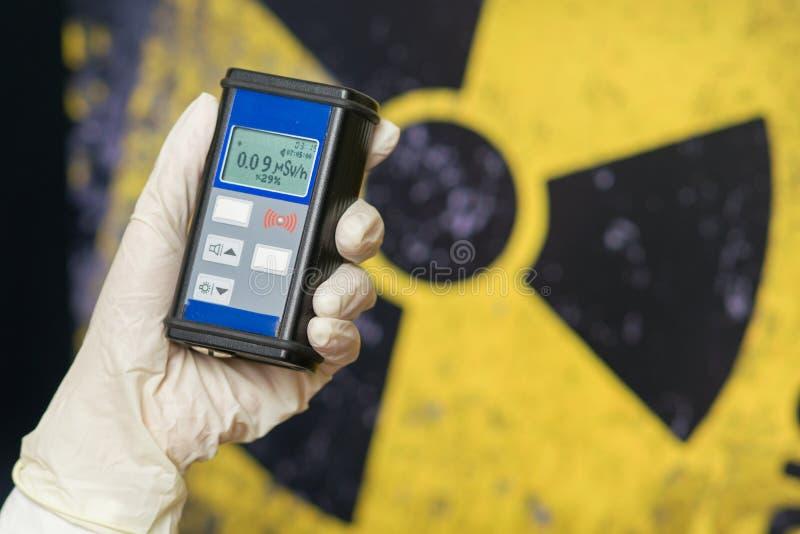 手套的辐射监督员与盖革计数器检查辐射的水平 免版税库存照片