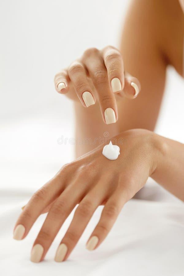 手奶油 关闭应用在皮肤的妇女的手化妆水 免版税库存照片