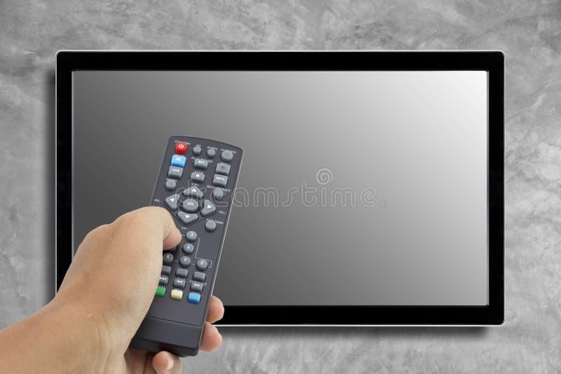 手对负遥控在电视屏幕 免版税库存照片