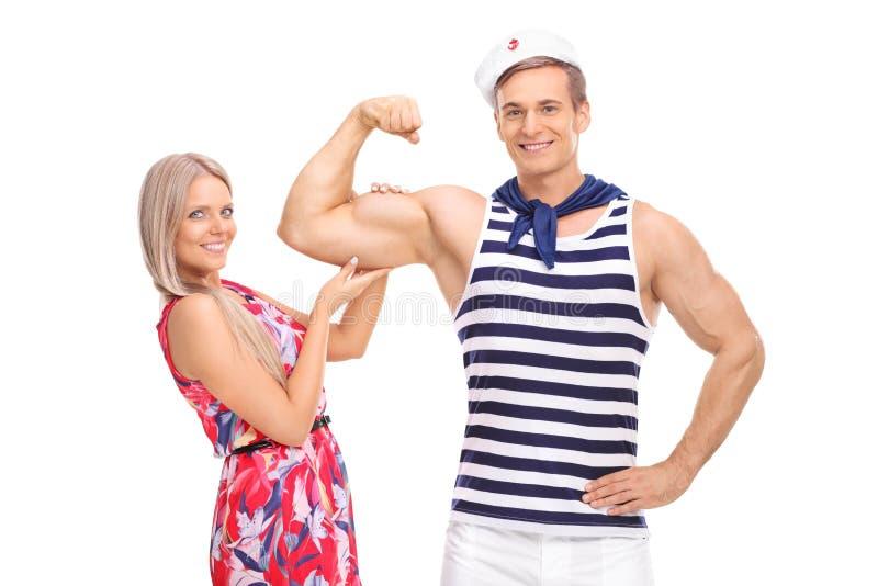 水手屈曲二头肌的和他的摆在与他的女朋友 免版税库存图片