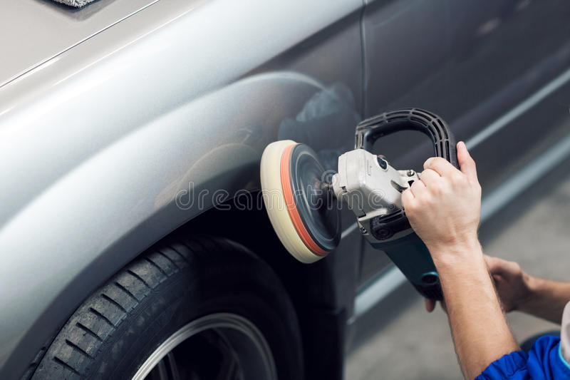 手工作者特写镜头使用磨光器的擦亮一个灰色车身在车间 免版税图库摄影