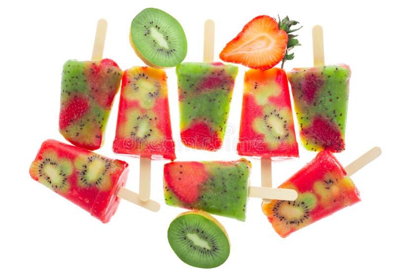 手工制造冰冰棍儿装饰了在白色背景和草莓隔绝的猕猴桃,概念素食食物 库存照片