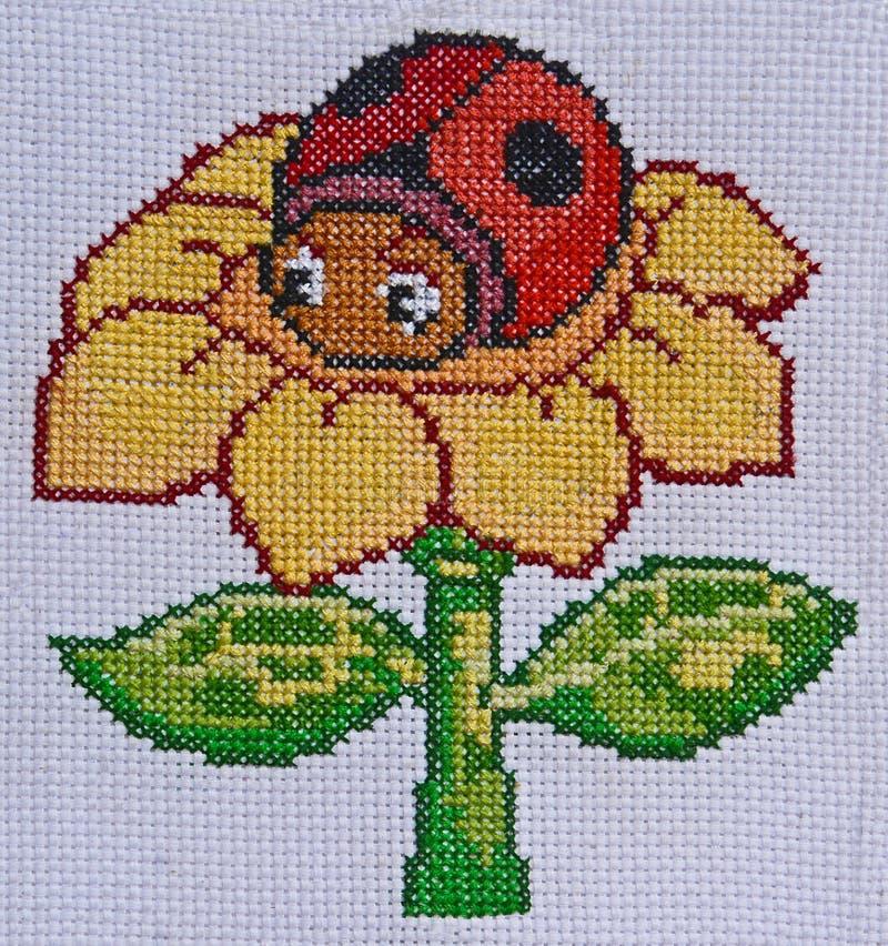 手工制造刺绣和十字绣花和瓢虫设计 图库摄影