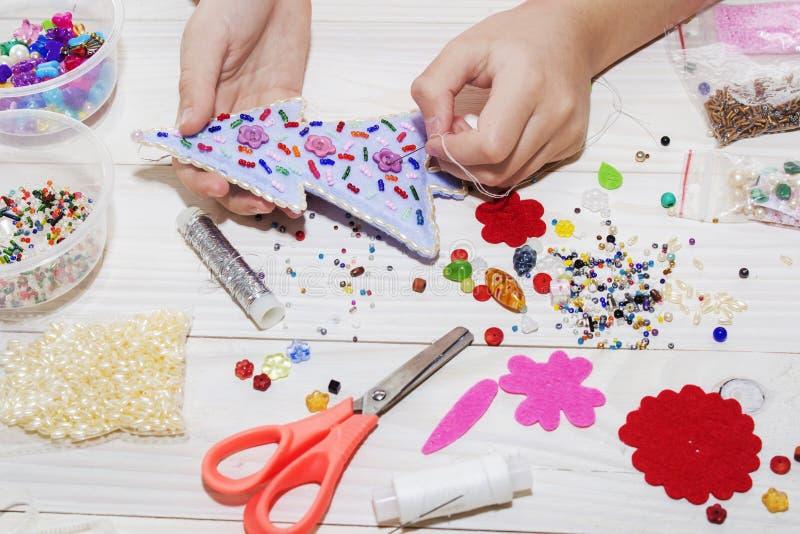 手工制造圣诞节玩具 逐步 缝合与毛毡和针的手工制造软的玩具的过程圣诞树的 免版税图库摄影