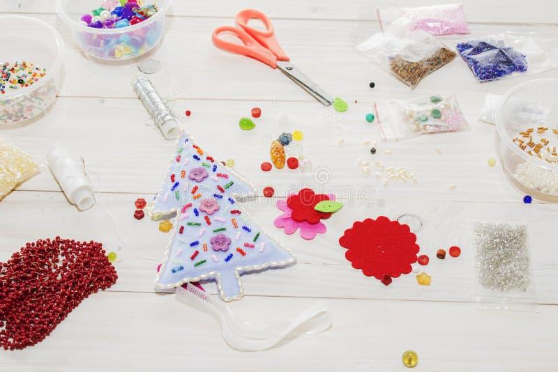手工制造圣诞节玩具 逐步 缝合与毛毡和针的手工制造软的玩具的过程圣诞树的 库存照片