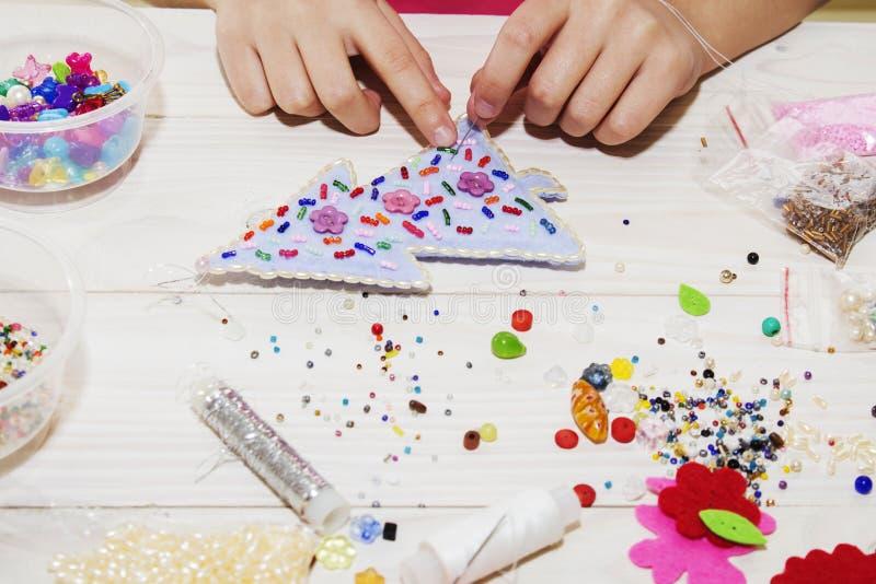 手工制造圣诞节玩具 逐步 缝合与毛毡和针的手工制造软的玩具的过程圣诞树的 图库摄影