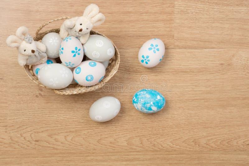 手工制造复活节彩蛋和兔子玩偶在被隔绝的篮子求爱 免版税图库摄影