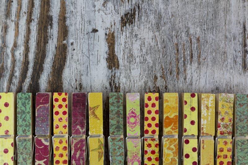 手工制造晒衣夹在木背景中 库存图片