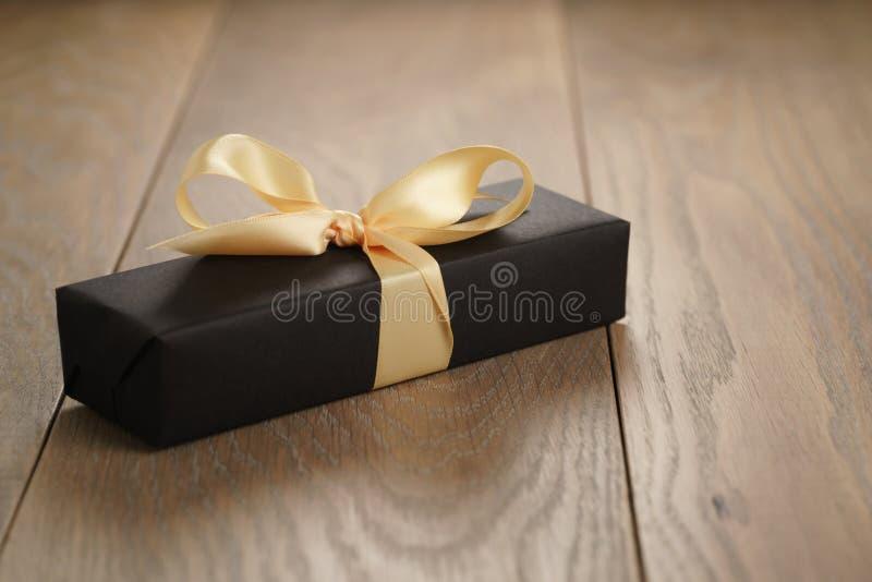 手工制造有黄色丝带弓的礼物黑色纸箱在木桌上 免版税图库摄影