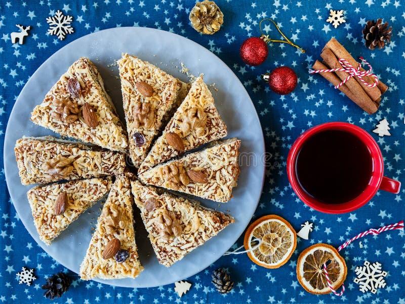 手工制造杏子饼片断在红色板材和红色杯子的用茶或咖啡与杉树,杉木,桂香在蓝色placemat 免版税库存图片