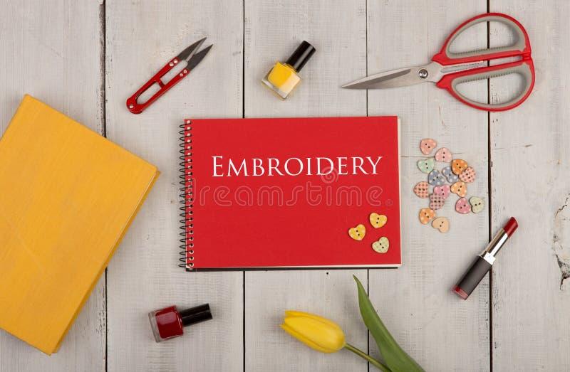 手工制造概念-缝合的剪刀、郁金香、红色笔记本有文本刺绣的,黄皮书、指甲油、唇膏和按钮 免版税库存照片