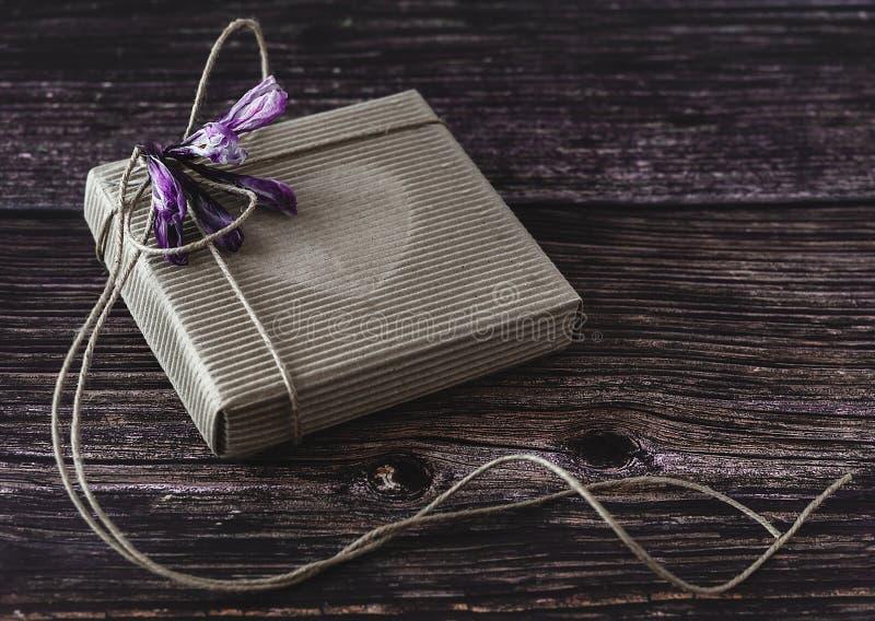 手工制造礼物概念 工艺纸回收有花的礼物盒在木桌上 r 免版税图库摄影