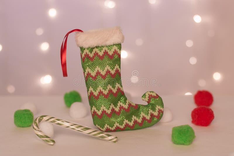 手工制造礼物立场的绿色长袜以圣诞灯、绿色糖果和软的球为背景 库存照片